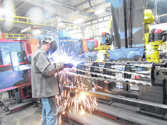 Doug Herring, an employee of Unverferth Manufacturing, welds blades into disks for a rolling tillage tool.