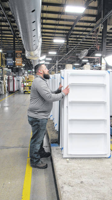 Whirpool of Ottawa team member Patrick Wills inspects doors before they are attached to upright freezer cabinets.