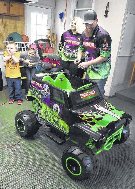 Zayvier Jones, 5, far left, and his sister Raelynn Dotson, 9, react after unveiling Zayvier's small Grave Digger monster truck on Thursday. Standing next to the truck is Krysten Anderson, driver of Grave Digger and Ricky Durden of the Monster Jam crew.
