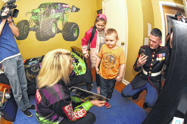 Zayvier Jones, 5, and his sister Raelynn Dotson, 9, react after seeing the Grave Digger facelift of his bedroom on Thursday while Krysten Anderson, driver of the Grave Digger holds a autographed pennant. Far right is Zayvier's dad, Lance Corporal Justin Jones.