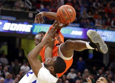Buffalo's Dontay Caruthers, bottom, drives to the basket against Bowling Green's Daeqwon Plowden during Saturday night's Mid-American Conference men's tournament title game in Cleveland. Plowden was called for the foul. Buffalo won 87-73. (AP photo)