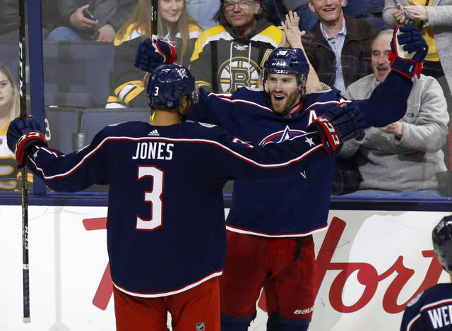 The Blue Jackets' Boone Jenner, right, celebrates his hat trick goal with teammate Seth Jones during Tuesday night's game against Boston in Columbus. The Blue Jackets won 7-4. (AP photo)