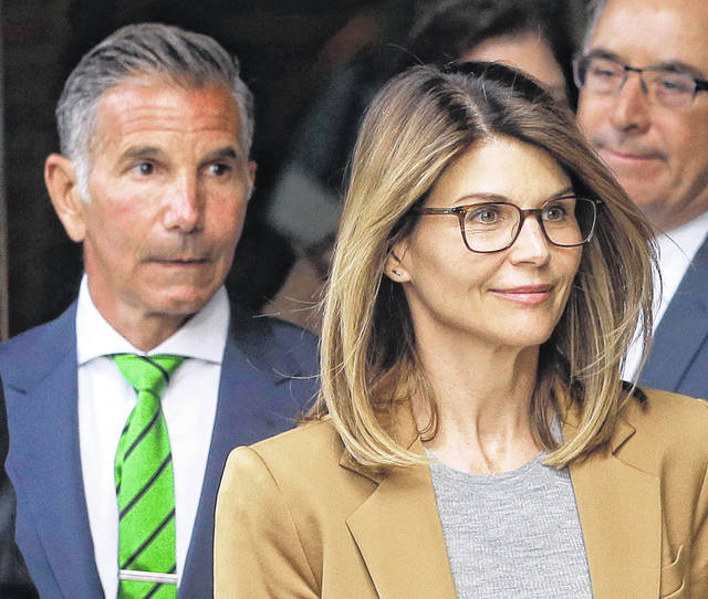 Actress Lori Loughlin, front, and her husband, clothing designer Mossimo Giannulli, left, depart federal court April 4 in Boston after facing charges in a nationwide college admissions bribery scandal. On Tuesday, Loughlin and Giannulli were among 16 prominent parents indicted on an additional charge of money laundering conspiracy in the case.