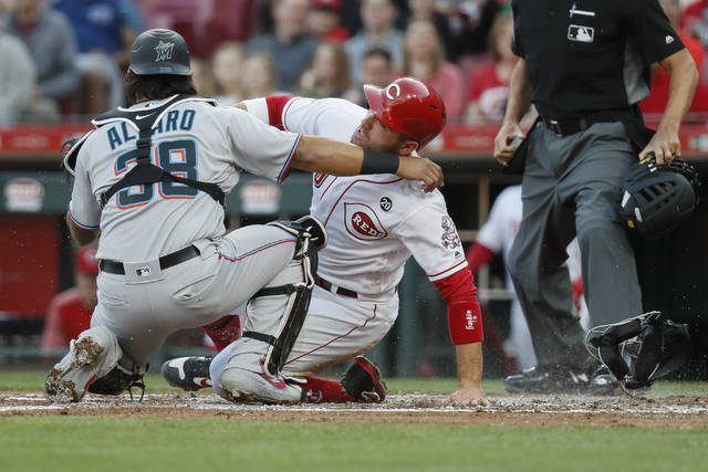 Miami Marlins catcher Jorge Alfaro (38) tags out Cincinnati Reds' Joey Votto, center, to complete a double play in the first inning of a baseball game, Wednesday in Cincinnati.