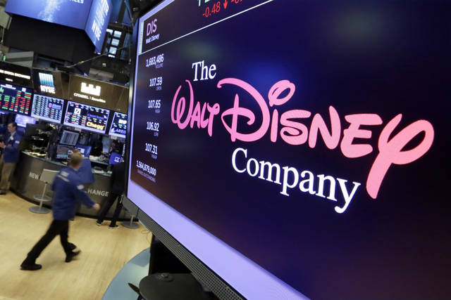 FILE - In this Aug. 8, 2017, file photo, The Walt Disney Co. logo appears on a screen above the floor of the New York Stock Exchange. On Thursday, April 11, Disney is unveiling details of its long-awaited streaming service Disney Plus. (AP Photo/Richard Drew, File)