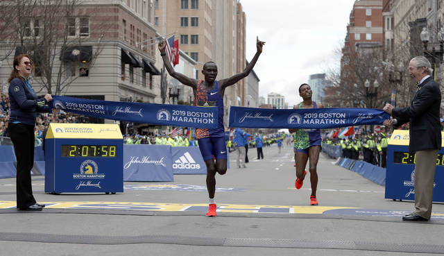 Lawrence Cherono, of Kenya, breaks the tape to win the 123rd Boston Marathon in front of Lelisa Desisa, of Ethiopia, right, on Monday in Boston.