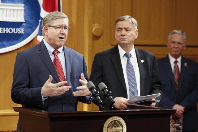 FILE - In this March 25, 2019 file photo, Ohio State Reps. Bob Cupp, R-Lima, left, and John Patterson, D-Jefferson, center, announce their proposed overhaul of Ohio's school funding formula at the Statehouse in Columbus.  Ohio lawmakers considering public input on proposed school-funding changes are hearing from lots of interested parties who say it's a solid start to the discussion but want more: more money for certain schools, more clarity on charter-school funding changes, more help for the economically disadvantaged. Ohio would increase spending on schools by an estimated $1.2 billion for a two-year period under a plan from lawmakers who studied the issue.  (AP Photo/John Minchillo, File)