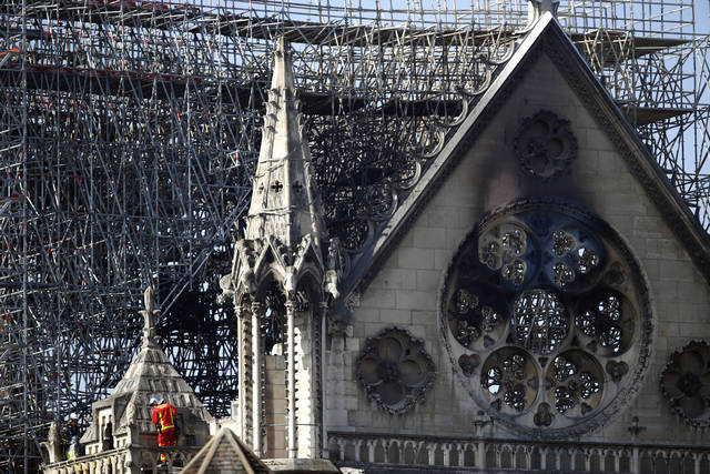 A firefighter makes his way on a balcony of Notre Dame cathedral Wednesday in Paris. Officials said a short circuit likely caused the fire that damaged the French landmark.