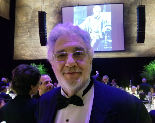 "Tenor Placido Domingo poses for a photo against the backdrop of himself as a younger singer as Verdi's ""Otello"" on Sunday at the Metropolitan Opera, in New York. Domingo has starred on the stage of the Metropolitan Opera for a whopping 50 years, and is still singing."