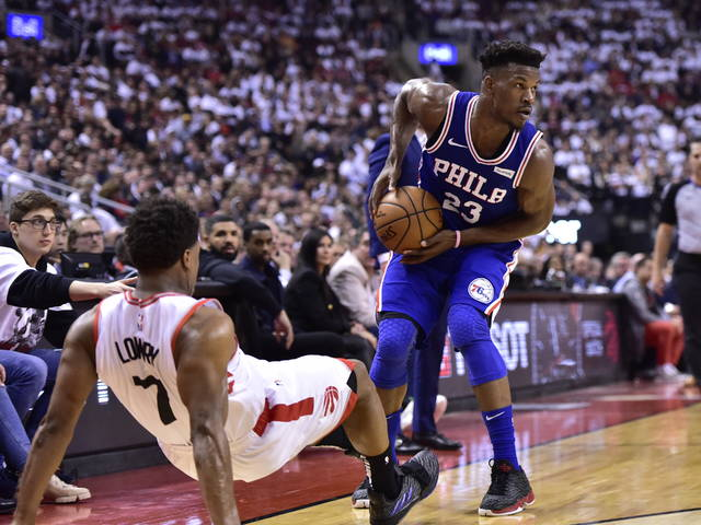 Philadelphia 76ers guard Jimmy Butler (23) looks to pass as Toronto Raptors guard Kyle Lowry (7) falls while defending during first-half, second-round NBA basketball playoff action in Toronto, Monday, April 29, 2019. (Frank Gunn/The Canadian Press via AP)