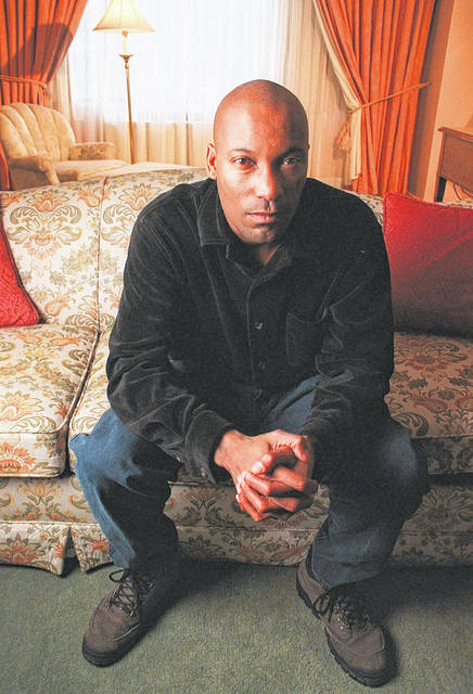 """This Feb. 9, 1997 file photo shows film director John Singleton posing in New York to promote his film """"Rosewood."""" The Oscar-nominated filmmaker died at 51, according to statement from his family Monday. He died after suffering a stroke almost two weeks ago."""
