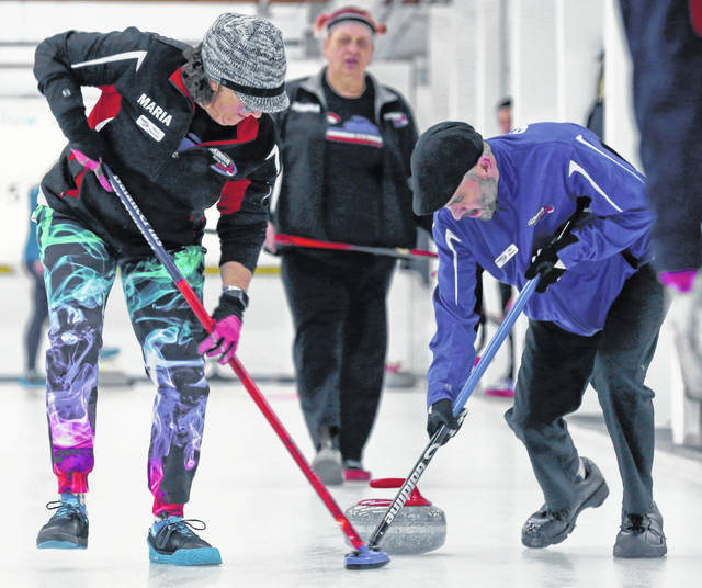 In this Saturday, April 6, 2019 photo, Maria Maxwell, left, and Kai Owens, right, sweep in front of a rock thrown by Jessika Dittler, back center, as the Owens Rink from Ohio compete during the 84th Fairbanks International Bonspiel Saturday afternoon, April 6, 2019 at the Fairbanks Curling Club in Fairbanks, Alaska.