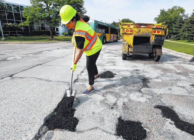 FILE - In an Aug. 6, 2018 file photo, Michigan Democratic gubernatorial candidate Gretchen Whitmer fills a pothole during a campaign event in Southfield, Mich. After passing waves of tax cuts in recent years, some Republican-dominated states have decided it's time to make a big exception, calling for tax increases to fix roads crumbling from years of low funding and deferred maintenance.