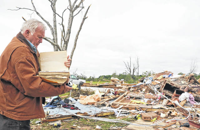 Robert Scott looks through a family Bible that he just pulled out of the rubble Sunday, April 14, 2019, from his Seely Drive home outside of Hamilton, Miss. after an apparent tornado touched down Saturday night, April, 13, 2019.