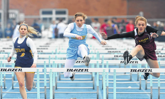 Ottawa-Glandorf's Caitlin Bockrath, left, Bath's Caitlyn Renner, center, and Kalida's Brenna Smith compete in the 100 meter hurdles during Friday night's Ehresman Memorial Track and Field Invitational.
