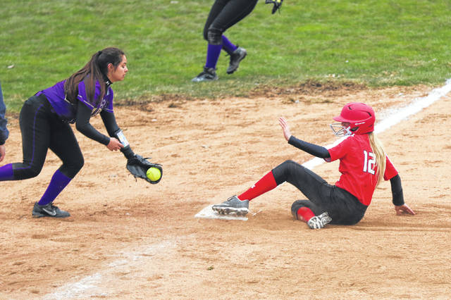 Bluffton's Haelyn Bischoff slides safely into third base before Ada's Kiersten Cortez can apply the tag during Thursday's game at Bluffton.