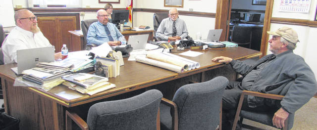 From left are Putnam County Commissioners Michael Lammers, John Schlumbohm and Vincent Schroeder discussing plans with Joe Hohlbein, Putnam County Recycling Center supervisor, to hire two full time employees and move the recycling operations to a larger building at its existing site.