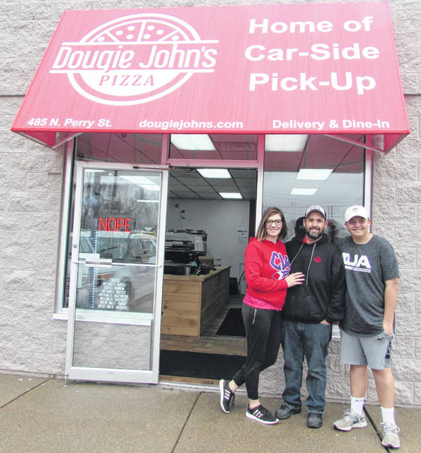 Kelly Craig and her husband Doug Craig, owner of Dougie John's Pizza, are pictured with their son Collin outside the Ottawa business that opened Tuesday.