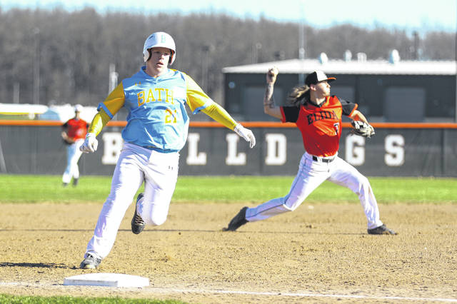 Bath's Cole Parlapiano rounds third base as Elida's Noah Adcock throws to first base during Tuesday's gameg at Elida.