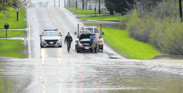 An Ohio State Highway Patrol trooper checks on a tow truck moving a car that had been stuck in high water Friday morning along Bluelick Road near Lima.