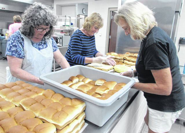 Clockwise from left Diane Myers, Deb Myers and Ruth Ellerbrock, Glandorf Elementary cooks, prepare 80 dozen rolls for a lunch for grandparents.