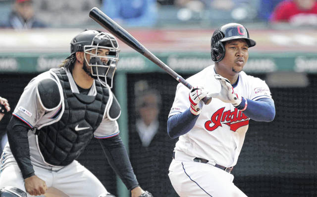 Cleveland Indians' Jose Ramirez, right, watches his ball after hitting a two-run double in the eighth inning of a baseball game against the Miami Marlins, Wednesday, April 24, 2019, in Cleveland. Jake Bauers and Francisco Lindor scored. Miami Marlins catcher Jorge Alfaro watches. The Indians won 6-2. (AP Photo/Tony Dejak)