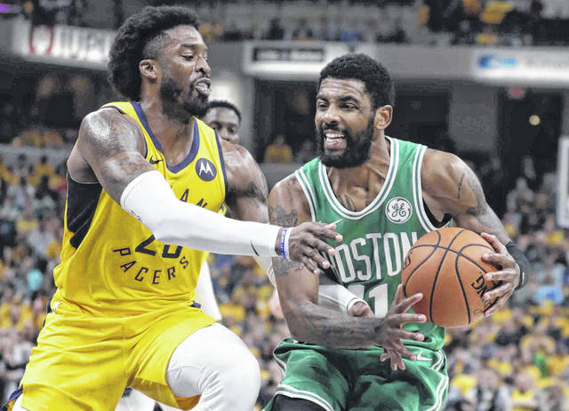 Boston Celtics guard Kyrie Irving, right, is fouled by Indiana Pacers guard Wesley Matthews, left,during the first half of Game 4 of an NBA basketball first-round playoff series in Indianapolis, Sunday, April 21, 2019. (AP Photo/Michael Conroy)