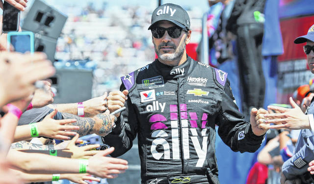 NASCAR Cup Series driver Jimmie Johnson (48) greets fans during driver introductions prior to the NASCAR Cup Series auto race at the Martinsville Speedway in Martinsville, Va., last month. Johnson is running in today's Boston Marathon.