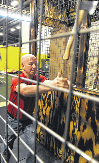 Kevin Wieging, president of Ultra Sound Special Events in Delphos, throws an axe inside his new indoor axe throwing range.