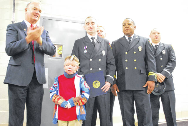 Landyn Douglas, who suffered burns over 50 percent of his body in a Lima home fire in November, is pictured with some of the firefighters who responded to the blaze.