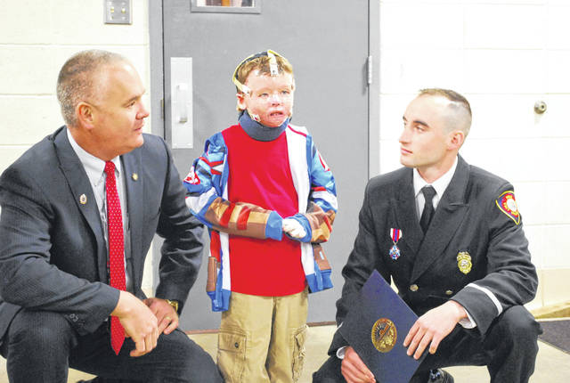 State Fire Marshal Jeff Hussey, left, and Lima firefighter Matt Hammons speak with 6-year-old Landyn Douglas during a ceremony Friday at the Lima Central Fire Station. Hammons was recognized for his heroics in rescuing Douglas from a burning home last fall.