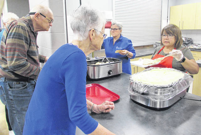Leipsic residents William and Carolyn Powell are served turkey and potatoes by from left, Nancy Rader and Irma Rodriguez, volunteers, during Thursday night's free community meal at Leipsic Community Center. Pictured are Miranda Wilson, Mercy Health LPN, and Eric Amstutz, Mercy Health nurse practitioner, preparing a scale for a free health clinic at Leipsic Community Center.