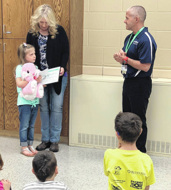Sydney Goodwin (left), 7, received a Life Saving Award and customized bunny from Doug LaRue (right), EMS Manager, and Lima Memorial Health System.