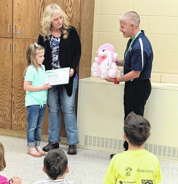 Sydney Goodwin (left), 7, received a Life Saving Award and customized Easter bunny from Doug LaRue (right), EMS Manager, and Lima Memorial Health System.