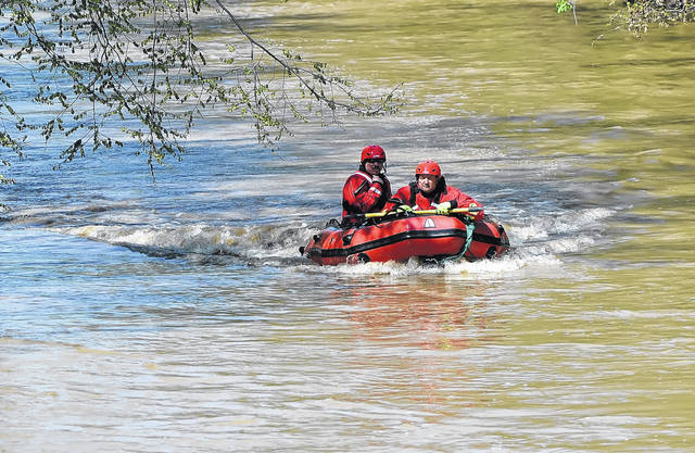 Rescue officials search the Ottawa River for a man who went in after his dog Sunday afternoon. The man was found deceased after a search of the river, which was faster moving than usual because of recent rains.