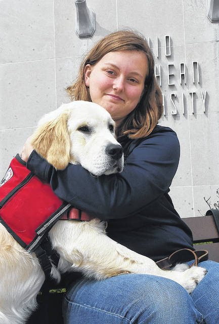 Ohio Northern University student Carah Porter works with a medical training dog, Chimichanga, in front of the Freed Center on the Ada campus.