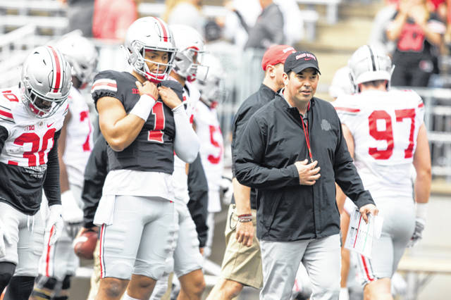 Quarterback Justin Fields (1) and coach Ryan Day watch during Saturday's spring game at Ohio Stadium in Columbus.