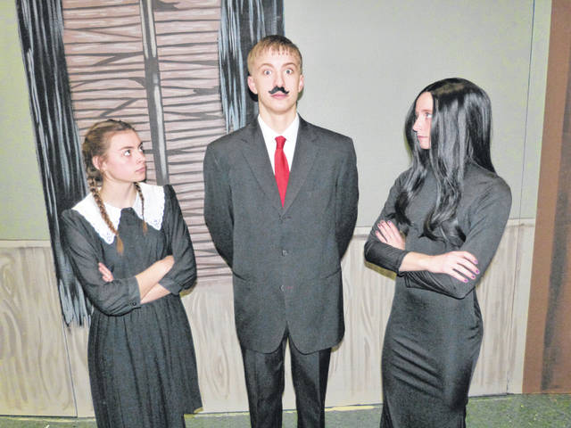 "Wednesday Addams, played by Madison Averesch, and Morticia, played by Quinley Schlagbaum, are unhappy with Gomez, played by Caden Edelbrock, in Ottoville High School's production of ""The Addams Family."""