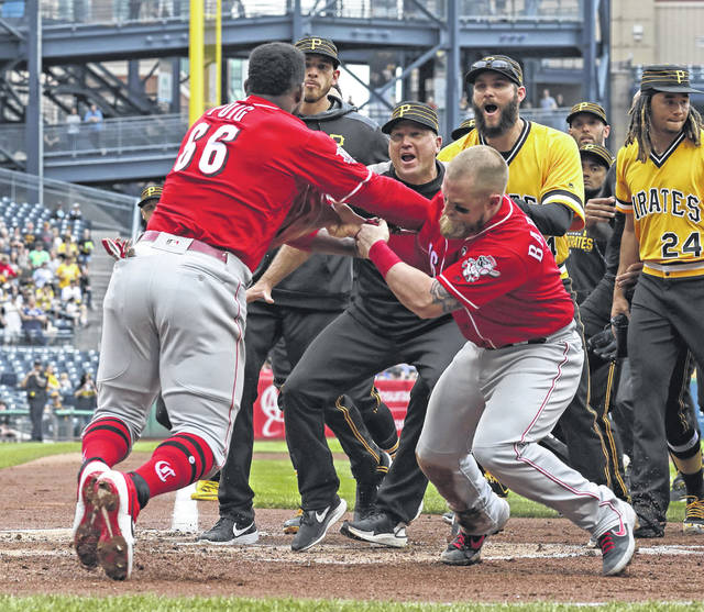 Cincinnati Reds outfielder Yasiel Puig (66) pulls away from Tucker Barnhart (16) and runs into Pittsburgh Pirates bench coach Tom Prince, center, as he attempts to re-enter a bench clearing during the fourth inning of Sunday's game.