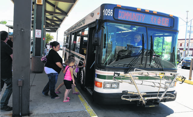 RTA bus driver, Gary Knepper, takes on passengers at the RTA station in downtown Lima. Craig J. Orosz | The Lima News