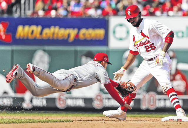 Cincinnati Reds shortstop Jose Iglesias dives to tag out St. Louis Cardinals runner Dexter Fowler (25) when Fowler's foot came off the bag after hitting an RBI-double during the eighth inning of Sunday's game.