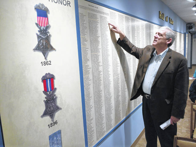 Amateur historian Larry Huffman looks over the list of names of veterans who were Medal of Honor recipients.