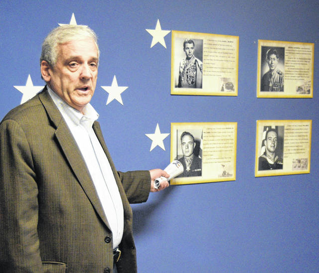 Larry Huffman points out some of the other Medal of Honor recipients that are highlighted in the Roll of Valor exhibit at the Allen County Museum.