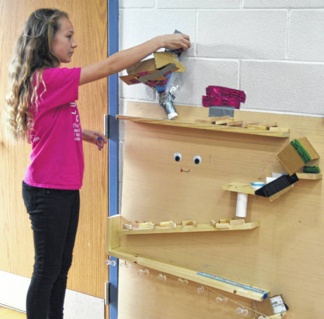 "Hailey Hahn, a seventh-grader from team ""Glitter Fam,"" demonstrates their Rube Goldberg machine at the annual STEAM Night at South Science & Technology Magnet School."