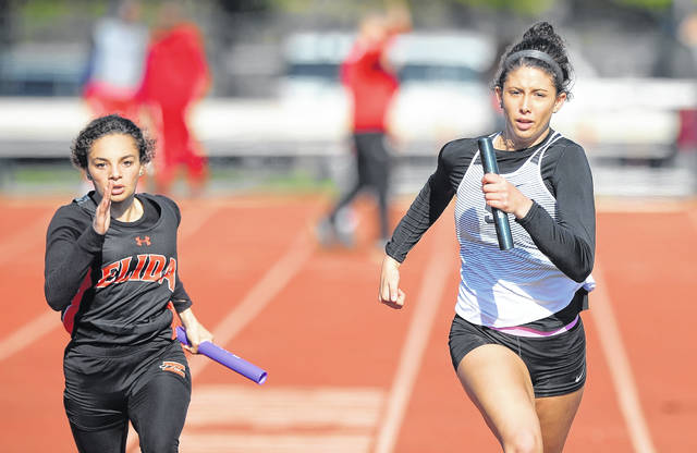 Spencerville's Nelaya Burden, right, runs ahead of Elida's Kylie Lewis in the 400 meter relay during Friday night's Shawnee Invitational.