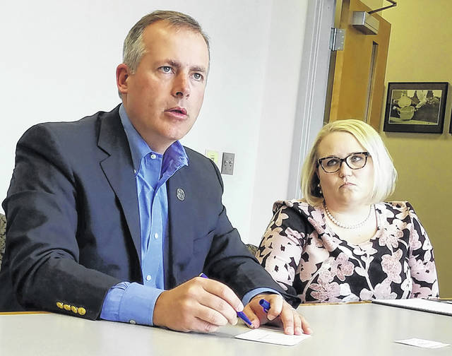 Ohio Treasurer Robert Sprague, left, of Findlay, draws a diagram of the up-front costs surrounding opioid rehabilitation while his press secretary, Brittany Halpin, watches Wednesday during a visit to The Lima News.