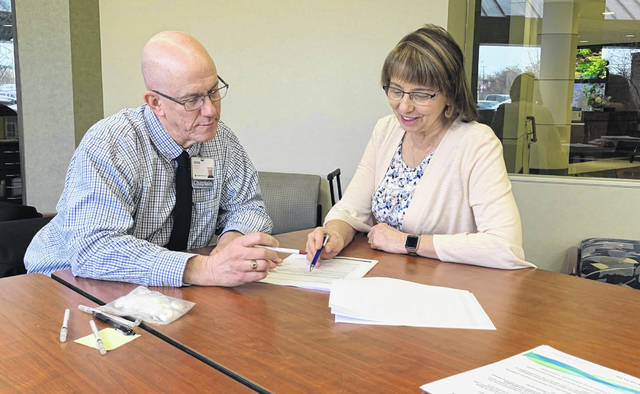 Herbert Wilker, Hospice/Homecare Chaplain, left, and Deb Warniment, Patient Advocate, right, go over a packet of advance directives forms at Mercy Health-St. Rita's Medical Center as part of the National Healthcare Decisions Day event Tuesday.