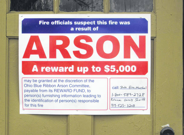 A sign alerts people that the State Fire Marshal's office has declared the fire at the Cloverdale Town Hall as arson and directs who to call with further information.