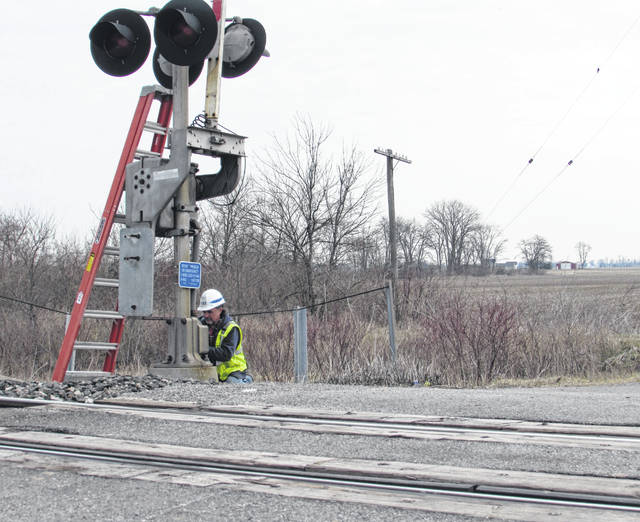 "A CSX Transportation employee works on what he called ""a yearly safety inspection"" on the railroad crossing at Road O and state Route 65 in Putnam County."