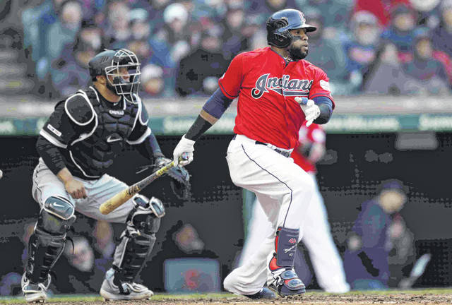 Cleveland Indians' Carlos Santana, right, watches his RBI-single off Chicago White Sox starting pitcher Ivan Nova in the sixth inning of a baseball game, Monday in Cleveland. Jose Ramirez scored on the play. White Sox catcher Welington Castillo, left, also watches the hit.